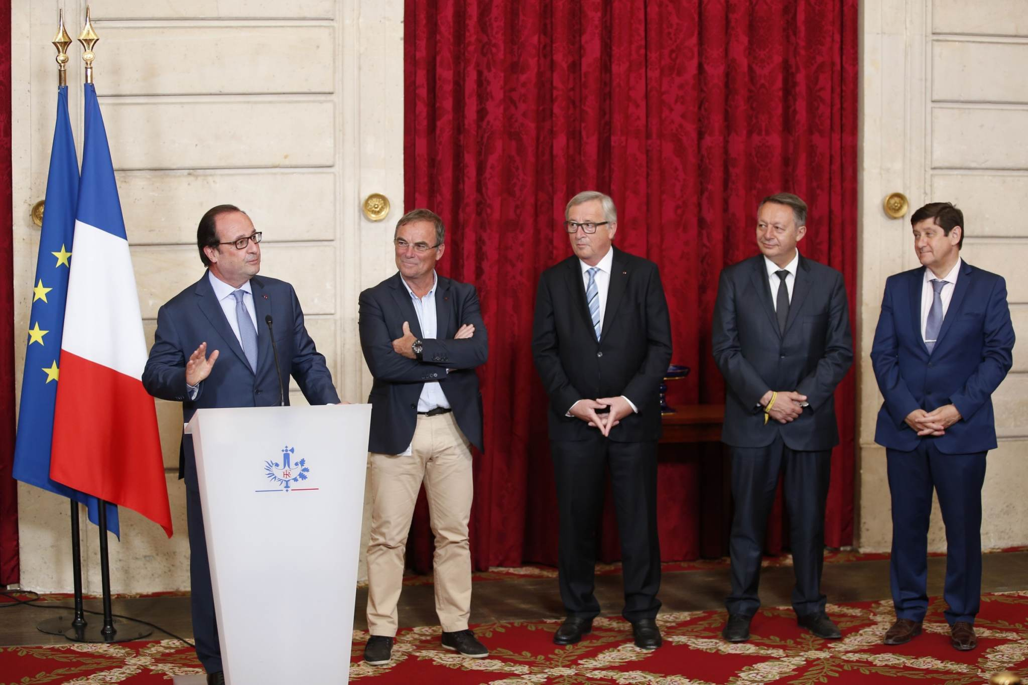 French president Francois Hollande (L) speaks next to French former cyclist Bernard Hinault (2L) during a ceremony rewarding him for his career as European Commission President Jean-Claude Juncker (C) and French Minister for Cities, Youth and Sport Patrick Kanner (R) listen on July 24, 2016 at the Elysee Palace in Paris. / AFP PHOTO / MATTHIEU ALEXANDRE
